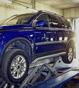 blue car on double horizontal car lift